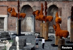 "People visit the sculptures of horses by Mexican artist Gustavo Aceves at Fori Imperiali (The Imperial Fora) during an exhibition called ""Lapidarium, Waiting for the Barbarians"" in Rome, Italy, Sept. 15, 2016."