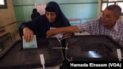 A polling station employee helps a female voter place her ballot in the correct box during parliamentary elections in Giza, Egypt, Oct. 18, 2015.