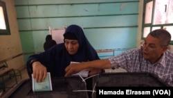 Một nhân viên phòng phiếu giúp cử tri bỏ phiếu vào hộp trong cuộc bầu cử quốc hội ở Giza, Ai Cập, ngày 18/10/2015.