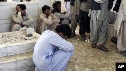 图为一名阿富汗人7月13日在卡尔扎伊弟弟的葬礼上悼念他