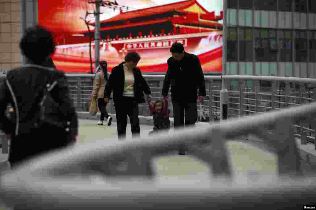 A family walks in front of a screen showing propaganda displays on a bridge in Shanghai, China, November 8, 2012.