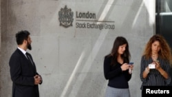 大眾站在倫敦證券交易所的入口處玩手機。(2018年8月23日)