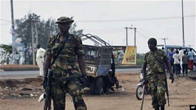 Soldiers stand guard outside the polling station during gubernatorial elections, Kaduna, April 28, 2011