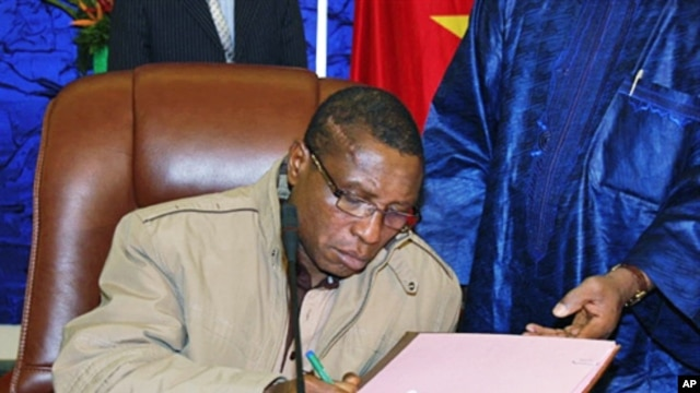 Guinean junta chief Captain Camara signs  pact on 15 Jan 2010 in Ouagadougou during a meeting with interim junta chief General Sekouba Konate and Burkina Faso President Blaise Compaore