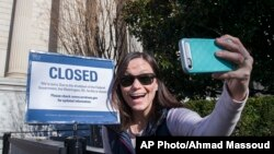 Jamie Parrish of Minneapolis takes a selfie in front of the closed sign at the National Archives, Dec. 22, 2018, in Washington. Congress' inability to approve a funding measure that includes money for a proposed U.S.-Mexico border wall has led to a partial government shutdown.