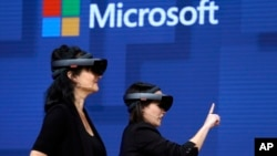 FILE- In this May 11, 2017, file photo, members of a design team at Cirque du Soleil demonstrate use of Microsoft's HoloLens device in helping to virtually design a set at the Microsoft Build 2017 developers conference in Seattle. Federal contract records
