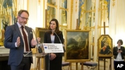 Great grandson of Richard Soepkez, Romanian Ion Florescu, left, speaks during a ceremony to return three paintings taken from their owners during World War ll, while France's culture minister Aurelie Filipetti, stands next to him at the Culture Ministry i