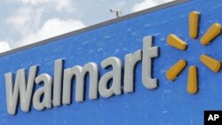 FILE- The Walmart sign is shown on June 1, 2017, in Hialeah Gardens, Fla.