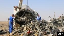 Dua petugas Rusia memeriksa puing-puing pesawat Metrojet A321 di Wadi al-Zolomat, daerah pegunungan di semenanjung Sinai, Mesir (2/11).