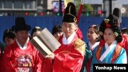 9일 한글날을 맞아 서울광장에서 열린 '세종마을 세종주간 축제'에서 세종대왕역을 맡은 김영종 종로구청장이 전달 받은 '훈민정음 해례본 복간본'을 들어 보이고 있다.