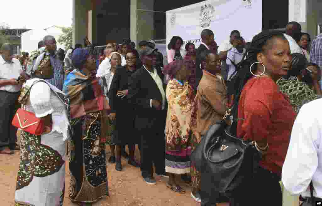 Voters queue up to cast their votes at a polling station as the country goes to the polls in Maputo, Mozambique, Oct. 15, 2014.