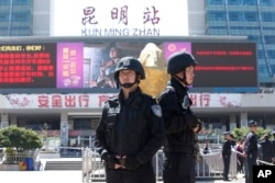 FILE - Armed police stand guard at China's Kunming railway station in Yunnan province, March 2, 2014. A day earlier, assailants slashed scores of people there, ultimately killing 31.