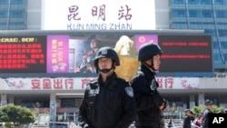 Polisi bersenjata berjaga-jaga di depan stasiun KA Kunming, Minggu (2/3). Meningkatnya penjagaan juga menyebar ke ibukota, Beijing.
