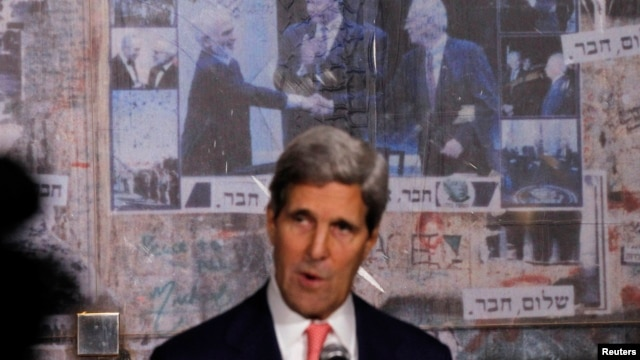 U.S. Secretary of State John Kerry stands in front of photo (L-R) showing Jordan's former King Hussein, former U.S. President Bill Clinton and Israel's former Prime Minister Yitzhak Rabin, as Kerry marks 18th anniversary of Rabin's assassination, in Tel Aviv, Nov. 5, 2013.