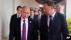 Presiden Rusia Vladimir Putin (kiri) berbincang dengan penguasaha aluminium Rusia, Oleg Deripaska.