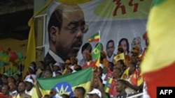 Supporters of the Ethiopian People's Revolutionary Democratic Front (EPRDF) sit in stands under a portrait of Prime Minister Meles Zenawi