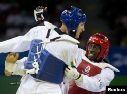 FILE - Mauro Sarmiento of Italy, in blue, and N'guessan Sebastien Konan of Ivory Coast fight during their men's preliminary round taekwondo match at the Beijing 2008 Olympic Games, Aug. 22, 2008.