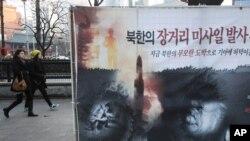 Poster na ulici Seula na kojem se vide izgladnela severno korejska deca i raketa, 24. januar, 2013.