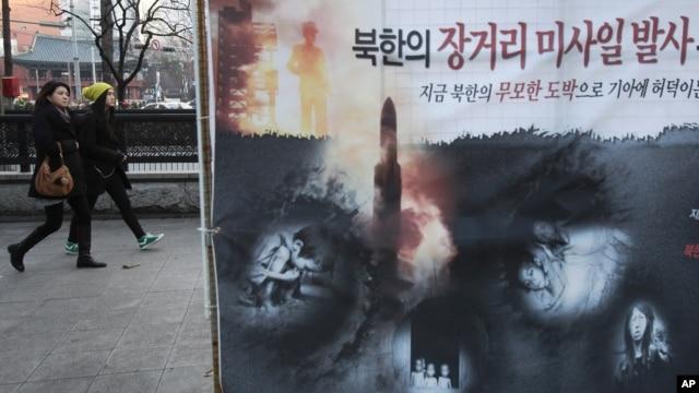 Spanduk memperlihatkan anak-anak Korut  yang kelaparan dan peluncuran roket Korut  terpampang di sebuah jalan di Seoul (foto: dok). Pejabat di Seoul dan Washington mengeluarkan peringatan serius atas uji coba nuklir Korut.