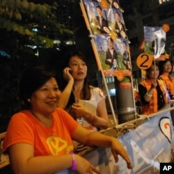 香港市民李小姐(左一)替區議會選舉候選人助選