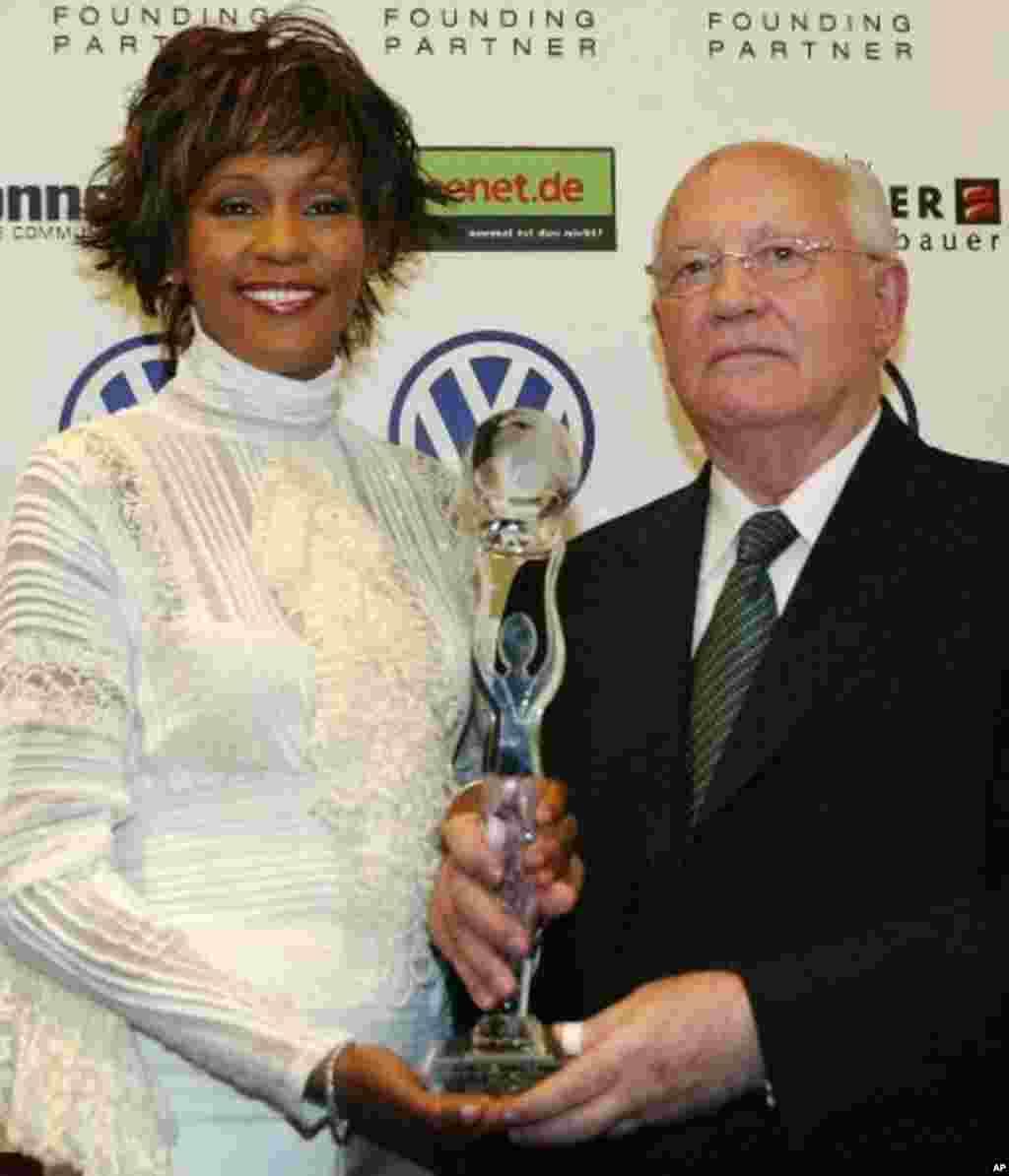Former Soviet President Mikhail Gorbachev, right, and US singer Whitney Houston pose with her award prior the beginning of the World Women's Award ceremony in Hamburg's Congress Center, northern Germany, Wednesday, June 9, 2004. Whitney Houston will rece