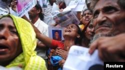 孟加拉製衣廠大樓倒塌﹐死傷者親屬拿著身份證明文件查詢消息。