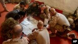 Tentara AS bersama tentara nasional Afghanistan membahas rencana serangan terhadap pemberontak Taliban di kamp Hanson, Afghanistan (13/6).