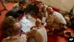FILE - A photo released by Operation Resolute Support headquarters shows U.S. Marines with Task Force Southwest and Afghan National Army soldiers planning for the continuation of offensive combat operations at Camp Hanson, Afghanistan, June 13, 2017.