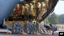 澳大利亚地勤人员准备从澳大利亚皇家空军C-17运输机上卸下搜索海面所需要的海鹰直升机, 2014年3月28日