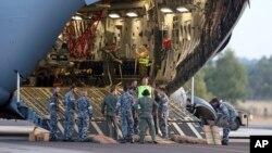 Para kru bersiap untuk mengeluarkan helikopter Sea Hawk dari pesawat Pasukan Kerajaan Australia C-17 sesaat setelah mendarat di Pangkalan Udara Militer RAAF Pearce di Perth, Australia (28/3), untuk membantu pencarian pesawat MH370 yang masih belum ditemukan hingga hari ini.