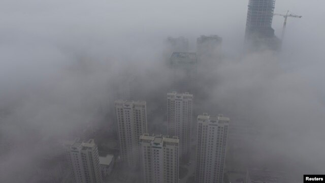Buildings are seen shrouded in heavy haze at Qingdao development zone, Shandong province, Feb. 25, 2014.