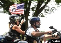 واشنگٹن میں 32 ویں سالانہ رولنگ تھنڈر میں شامل ایک سابق فوجی اپنی موٹر سائیکل پر قومی پرچم کے ساتھ۔