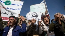 Yemenis chant slogans during a protest against caricatures published in French magazine Charlie Hebdo in front of the French Embassy in Sanaa, Yemen, Saturday, Jan. 17, 2015.