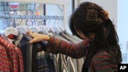 Afghan fashion designer Zolaykha Sherzad looks through clothing from her label Zarif Designs at a London boutique