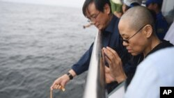 Liu Xia, the wife of Chinese Nobel Peace Prize laureate Liu Xiaobo, watches as Liu's ashes are buried at sea off the coast of Dalian in northeastern China's Liaoning Province, July 15, 2017. China cremated the body of Liu on Saturday, July 15, 2017. (Shenyang Municipal Information Office via AP)
