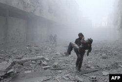 FILE - A wounded man is carried following an air strike on the rebel-held besieged town of Arbin, in the eastern Ghouta region on the outskirts of the capital Damascus on January 2, 2018.