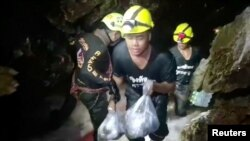Rescuers carry supplies into the Tham Luang cave complex, where 12 boys and their soccer coach are trapped, in the northern province of Chiang Rai, Thailand, July 5, 2018.