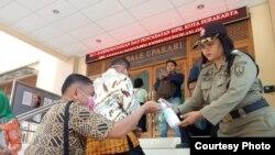 Warga yang mengurus administrasi kependudukan diminta mencuci tangan dengan hand sanitizer yang disediakan Pemkot Solo, Senin, 16 Maret 2020. (Foto: Humas Pemkot Surakarta)