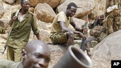 SPLM North rebels practice with a mortar as others watch along the border in South Kordofan, Sudan.