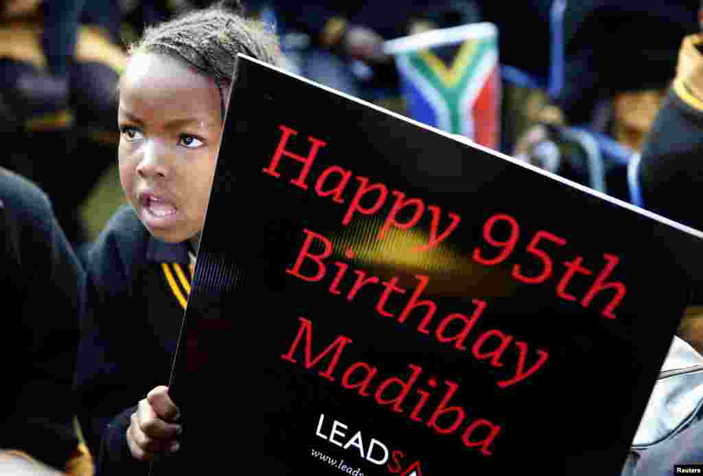 Children hold placards as they gather to wish to Nelson Mandela happy birthday at a township school in Atteridgeville, near Pretoria, July 18, 2013.
