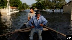 Victor Ferreira, who was displaced by flooding, rows his boat through the streets of his Jukyty neighborhood in Asuncion, Paraguay, Dec. 23, 2015. The Paraguay River is at its highest level since 1984.