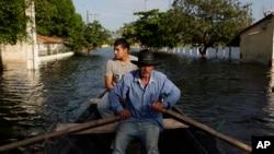 2015年12月23日巴拉圭首都地区水位大幅上涨 当地一位居民被迫以船代步。