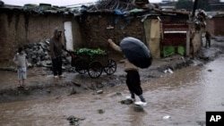 FILE - Pakistani man crossing flooded path during heavy rain fall in slum on outskirts of Islamabad, Pakistan.