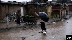 FILE - Pakistani man crossing flooded path during heavy rain fall in slum on outskirts of Islamabad, Pakistan.