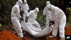 Trabajadores de la salud entierran el cuerpo de una mujer que supuestamente murió por ébola en Liberia.