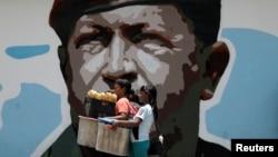 Women walk past a portrait of Venezuela's late President Hugo Chavez in Caracas, Venezuela August 7, 2017.