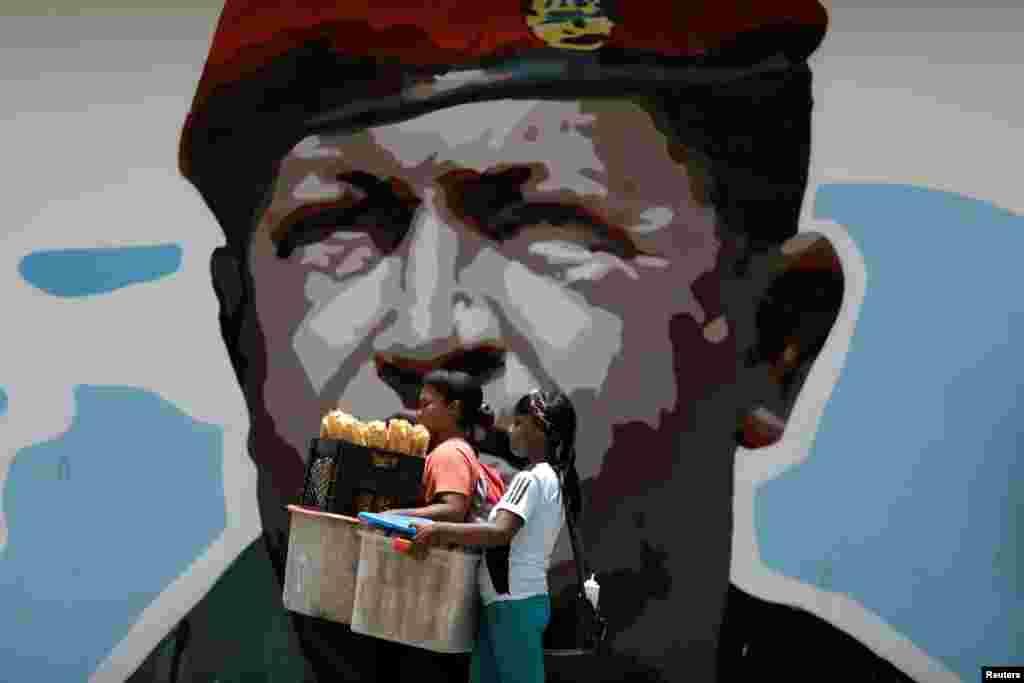 Dua penjaja makanan melewati lukisan potret mendiang Presiden Venezuela Hugo Chavez di Caracas.