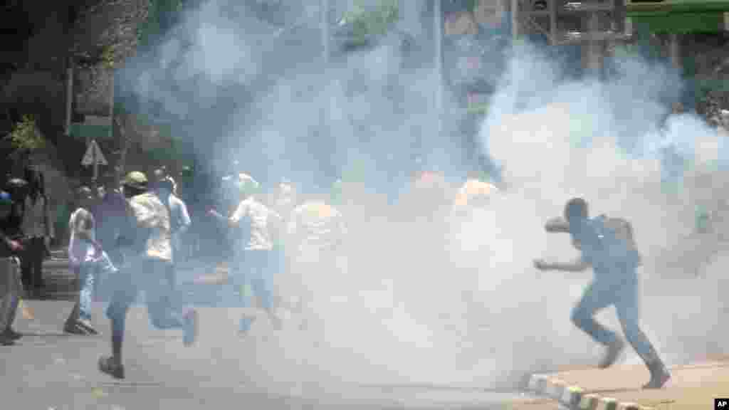 University students run as police use tear gas to disperse them during a demonstration in Nairobi, Kenya, Tuesday, Sept, 22, 2015.