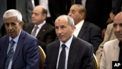 FILE - Mustafa Abdel Jalil, leader of the National Transitional Council (NTC) waits for the final results of the Libyan elections in Tripoli, July 17, 2012. The NTC allegedly received funds from the defendants on trial in UAE. Their lawyer says they are being used as political pawns.