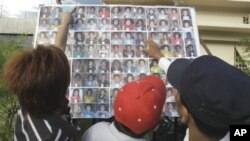 A Cambodian man compares a photo to those of stampede victims at Preah Kossamak Hospital in Phnom Penh, Cambodia, 24 Nov 2010